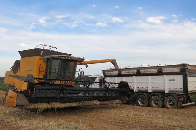 Colhedeira amarela descarregando soja em caminhão caçamba branco
