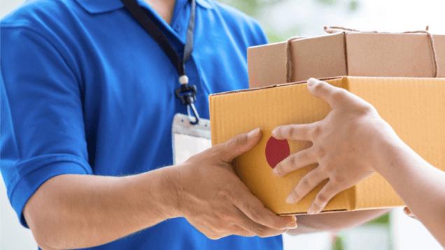 Homem com roupa azul entregando caixas para outra pessoa