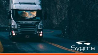Caminhão na estrada com título Aprenda a averbar seguro de carga de forma automática