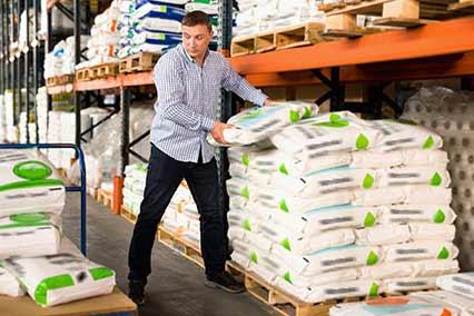 Homem carregando adubo em loja agropecuaria